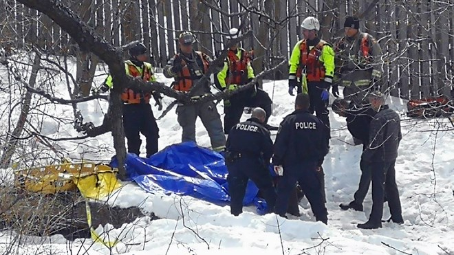 Emergency responders remove a body found in Junction Creek off Riverside Drive on April 11. (Arron Pickard / Sudbury.com)