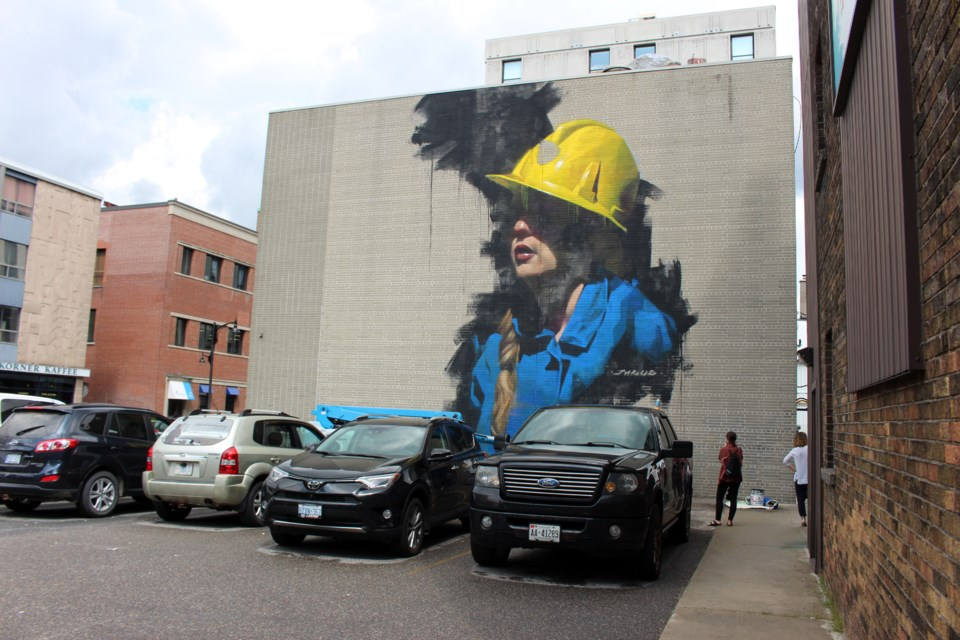 Internationally-renowned muralist Jarus pays tribute to his grandfather, who was a Sudbury miner, by painting this portrait of a female miner at the corner of Lisgar and Larch streets. The photo-realistic painting is just one of the art installments to hit Sudbury's downtown core as part of the Up Here festival that takes place 18-20. (Heather Green-Oliver/Sudbury.com)