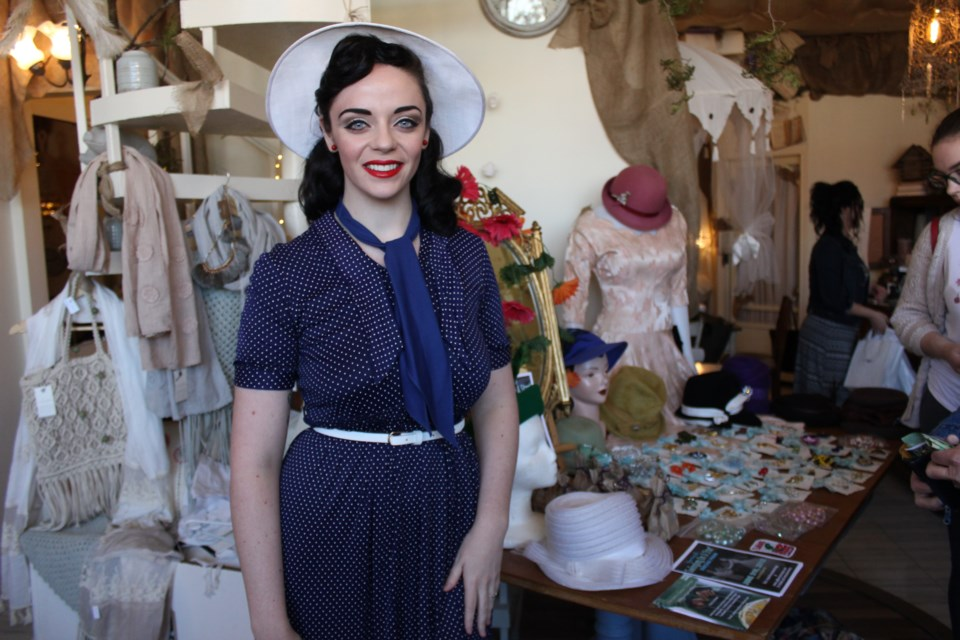 Sporting a classic blue dress with white polka dots and a matching hat, Starlotte Satine channels vintage chic at a pop-up shop at Cedar Nest recently. Her vintage pop-up shop, Starlotte Satine Fashions, is your connection to classic mid-20th century fashion. (Ella Jane Myers)