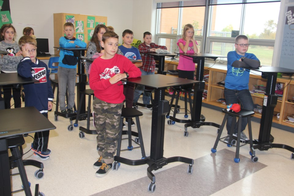 Grade 5 students at École publique de la Découverte demonstrate their classroom's standing desks. Photo by Heidi Ulrichsen.