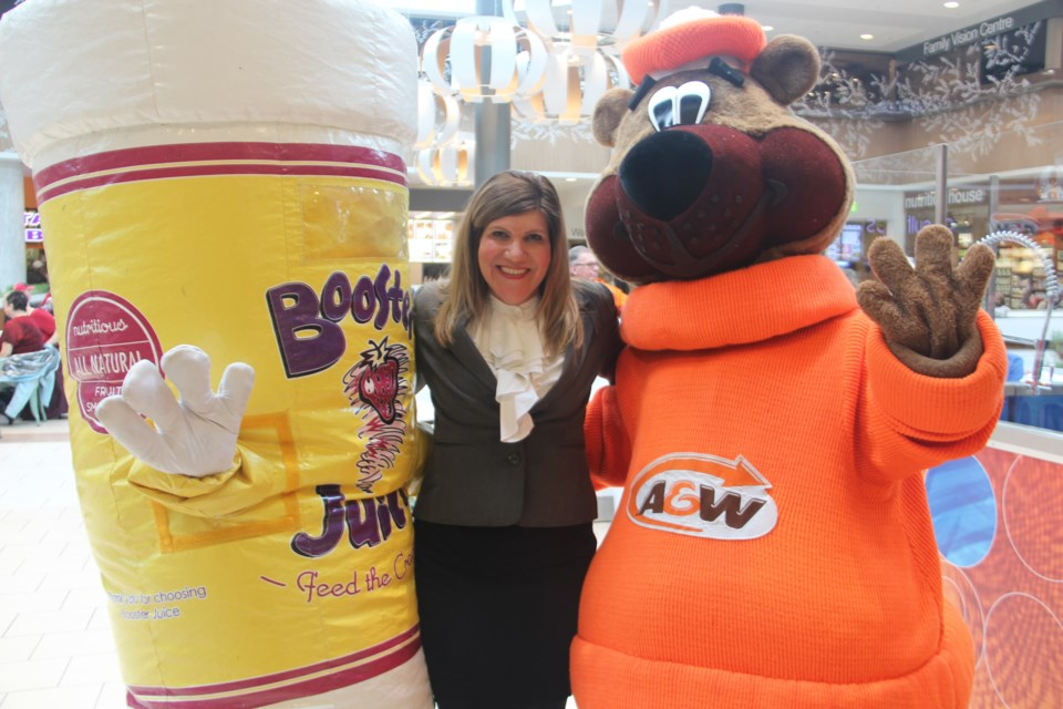 New Sudbury Centre general manager Jenny Beckerton poses with Cuppy (the mascot for Booster Juice) and the A&W Root Bear at a Feb. 28 celebration of the completion of renovations to the mall's food court. Photo by Heidi Ulrichsen.
