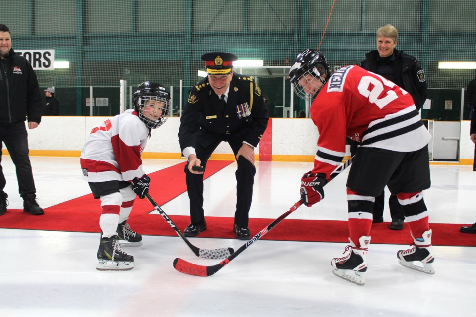Greater Sudbury Police Services officially dropped the puck for the 10th anniversary of the Police Cup hockey tournament. Pictured left to right: Cedar Park Red Wings player Dane Nielson, Chief Paul Pedersen and Algonquin Hawks player Cohen Neldor. (Heather Green-Oliver/Sudbury.com)