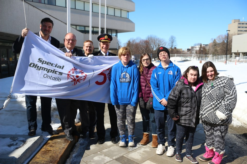 Helping to hoist the 50th anniversary Special Olympics Ontario flag at Tom Davies Square on Monday was, from left, Sudbury Wolves owner Dario Zulich, mayor Brian Bigger, Special Olympics Sudbury sports and competition developer Jarrod Copland, Greater Sudbury Police Chief Paul Pedersen and Special Olympics athletes Krystin Albert, Josée Seguin, Kole O'Malley, Danie Houle and Shannon O'Reilly. (Arron Pickard)