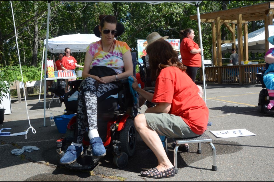 ICAN client Elizabeth Kerstens gets her wheelchair washed by Carmen Sampson, manager of client services, during ICAN's 40th anniversary celebration. (Arron Pickard/Sudbury.com)
