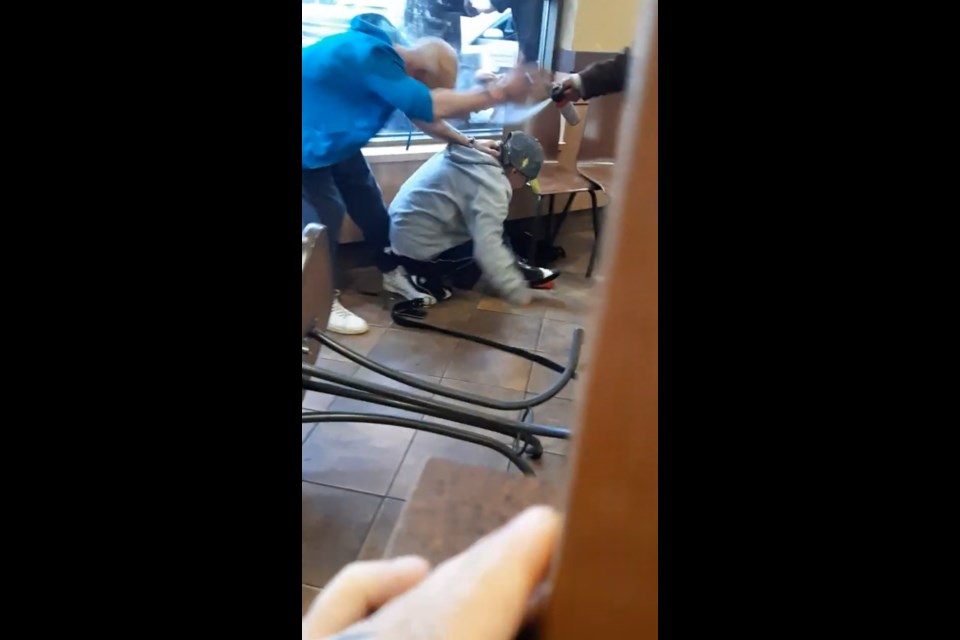 As the knife-wielding man holds a woman by the neck on her knees, video from another Tim Hortons customer captures the moment bear spray was used to try to stop him. (Screen capture)