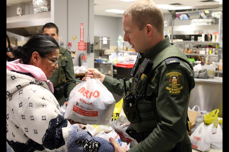Ministry of Natural Resources and Forestry conservation officer, Davis Viehbeck, hands out moose meat at the RFDA on Wednesday.