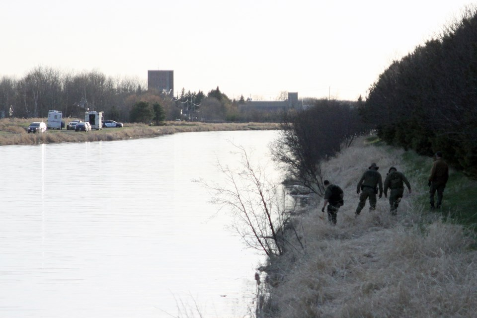 Officers search the north bank of the McIntyre River after the OPP's underwater search and recovery unit found a body in the river on Thursday. (Matt Vis, tbnewswatch.com)