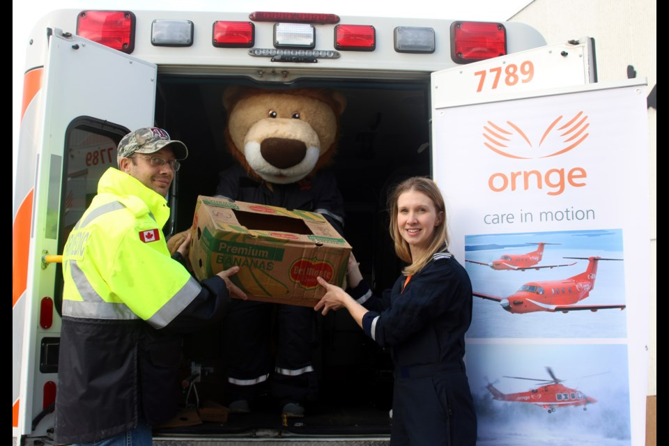 Daryl Parfeniuk (left) and Tegan Fletcher (right), paramedics with Ornge, help load an ambulance with food donations in support of the Regional Food Distribution Association during the Fill an Ambulance Food Drive.