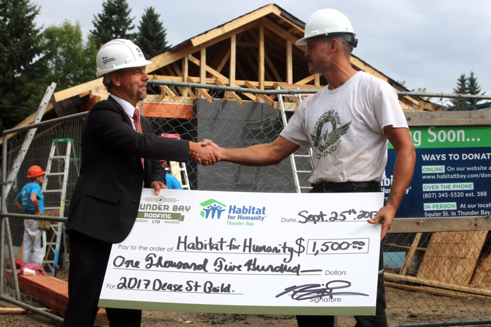 Neil Hrabowy (right), owner of Thunder Bay Roofing, donates $1,500 to Habitat for Humanity Thunder Bay, in addition to providing the roof on its 2017 build.