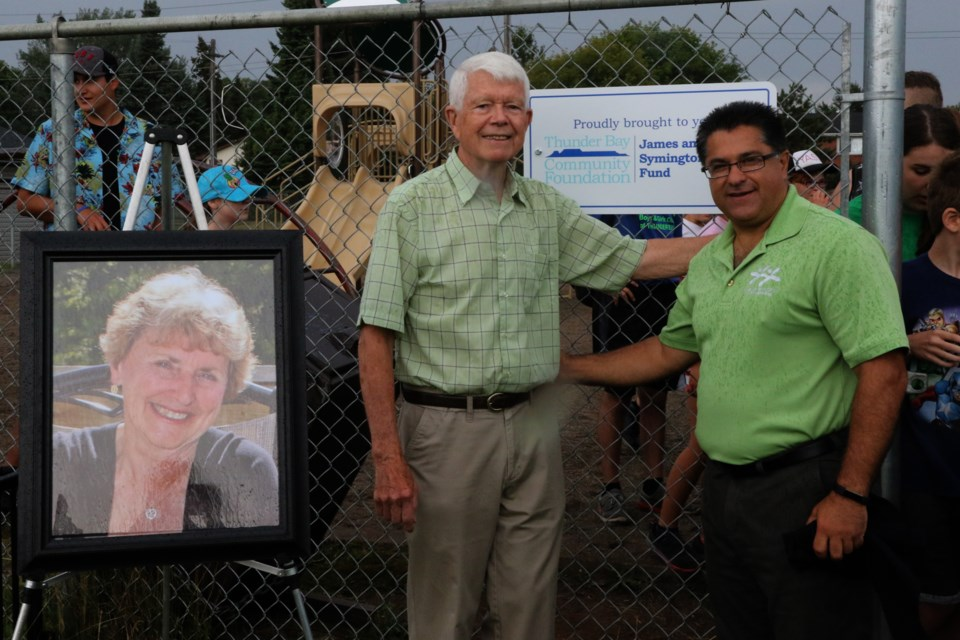 Jim Symington (left) and executive director Albert Aiello stand next to a portrait of the late Shirley Symington at the unveiling of the Boys and Girls Club play structure. (Michael Charlebois, tbnewswatch)
