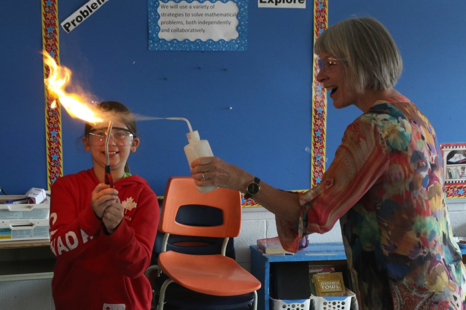 Samantha Bradley (left) and Patyy Hajdu light a flame at Science North summer camp at Vance Chapman Public School. (Michael Charlebois, tbnewswatch)