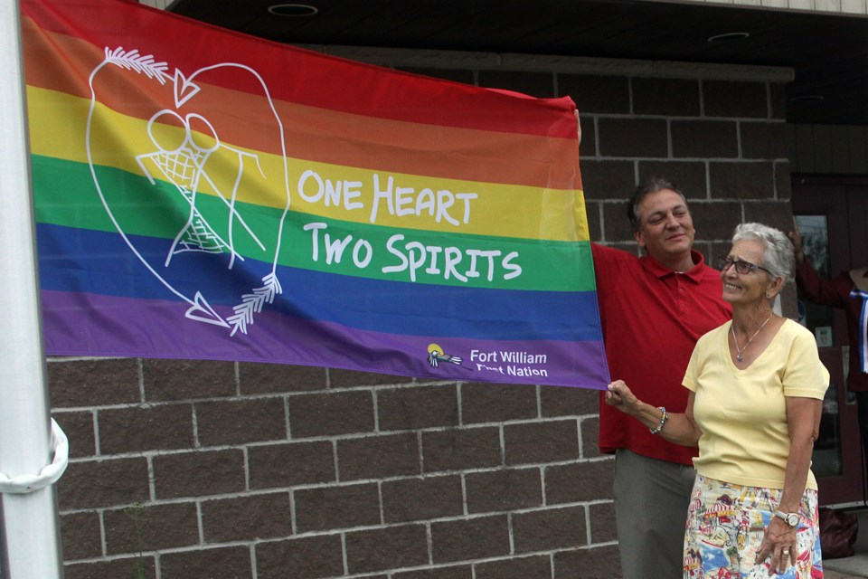 Flag designer Lorraine Bannon and community member Raili Saarinen display the pride flag recognizing the two-spirited community that was raised outside the Fort William First Nation office on Wednesday, July 11, 2018. (Matt Vis, tbnewswatch.com)