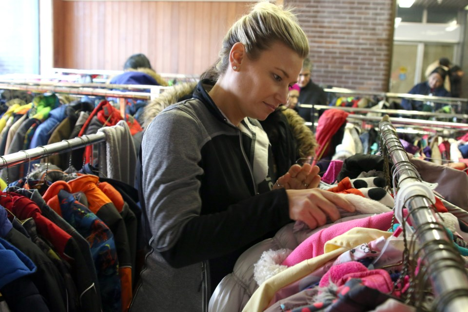 Volunteer Jacqui Workman helps sort through hundreds of coats donated to the Kids for Coats Giveaway on Saturday. (Photos by Doug Diaczuk - Tbnewswatch.com).