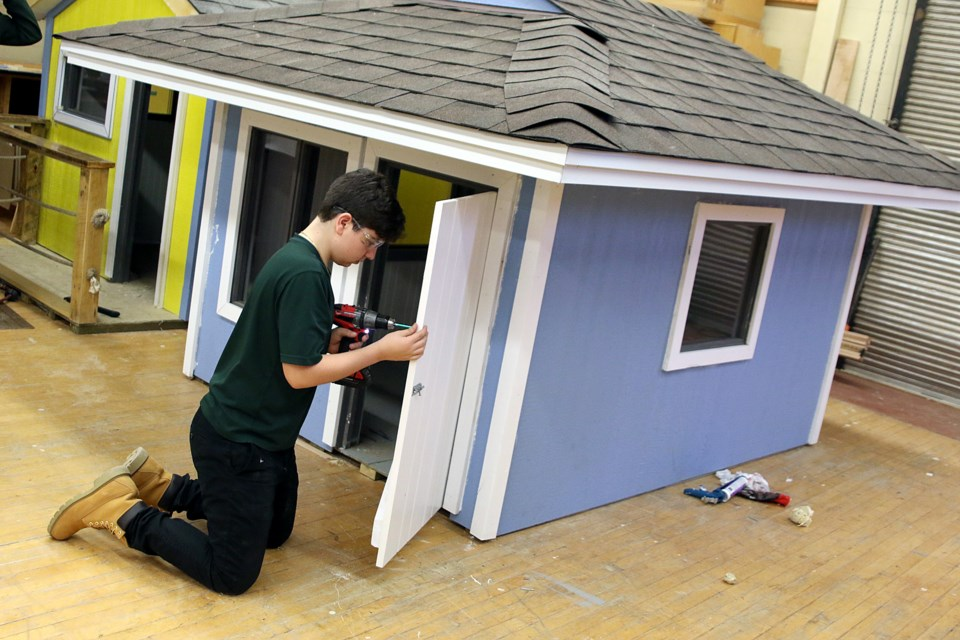 St. Patrick High School Grade 11 student Josh Bisignano on Friday, Nov. 30, 2018 puts the finishing touches on a playhouse he and classmates built to donate to The Thunder Bay Children's Centre Foundation for an upcoming raffle. (Leith Dunick, tbnewswatch.com)