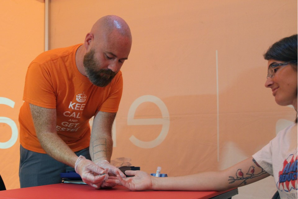 Kyle Lees administering a blood test to Tonya Muchano inside the Elevate NWO tent at Victoriaville mall. (Michael Charlebois, tbnewswatch)