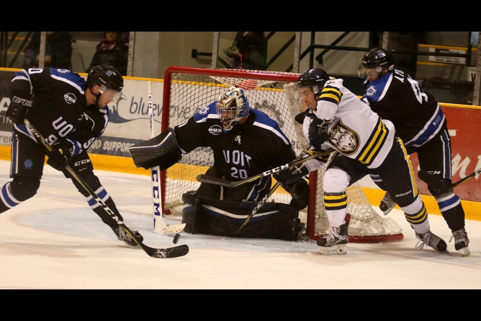 Grant Valiquette attempts to wrap the puck around the net and past UOIT goaltender Tyson Teichmann on Saturday, Sept. 30, 2017 at Fort William Gardens (Leith Dunick, tbnewswatch.com).