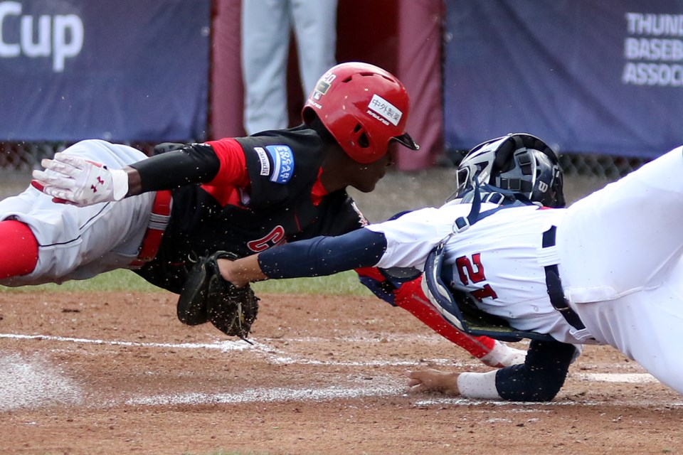 Canada's Denzel Clarke (left) is tagged out at the plate in the second inning by a diving American catcher Anthony Siegler on Thursday, Sept. 7, 2017 at Port Arthur Stadium (Leith Dunick, tbnewswatch.com).