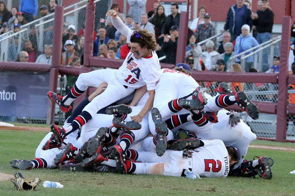Reynaldo Delgado (15) piles on top of the celebration after United States downed Korea 8-0 in the gold-medal game at the Under 18 World Baseball Cup at Port Arthur Stadium (Leith Dunick, tbnewswatch.com).