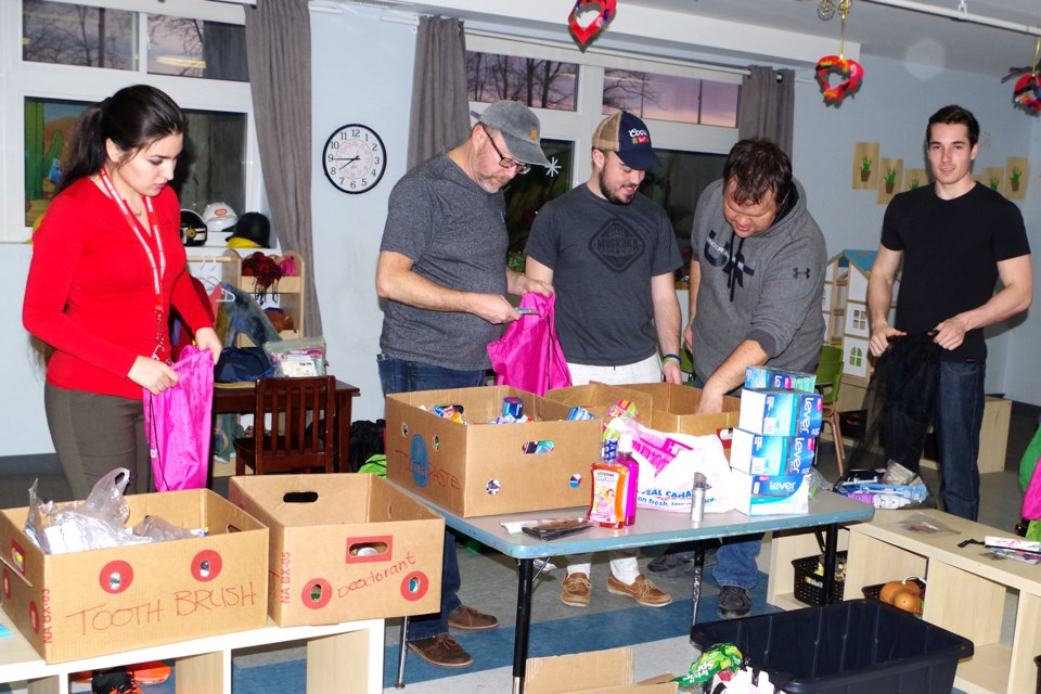 Pictured (l-r) Sasar Manafi,  Chaplain Allan Gallant, Tyler Rigby, James Symons, and Noah Chasse, pack up products for homeless youth. Bob Liddycoat / Thorold News