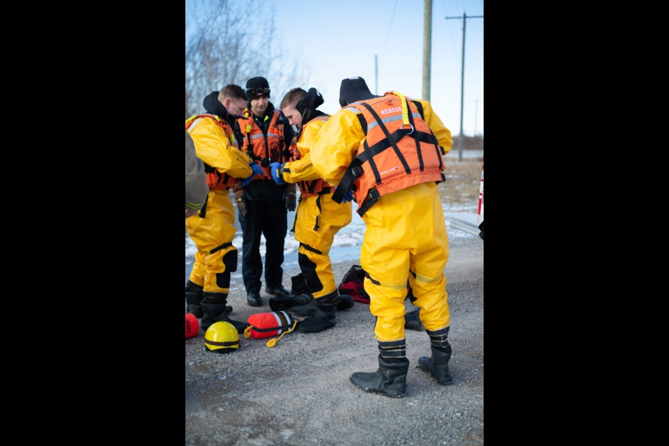 Firefighters Brad Reed (l) and Park Reilly (r) make sure every zipper is zipped and flap folded on their dry suits before entering the water as firefighter and Technical Reserve Lead Mark Todorov (c) checks their work. Doug Youmans for ThoroldNews
