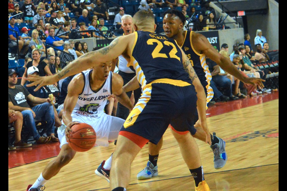 Point guard Trae Bell-Haynes drives between two defenders. Stephen Dyell / Thorold News