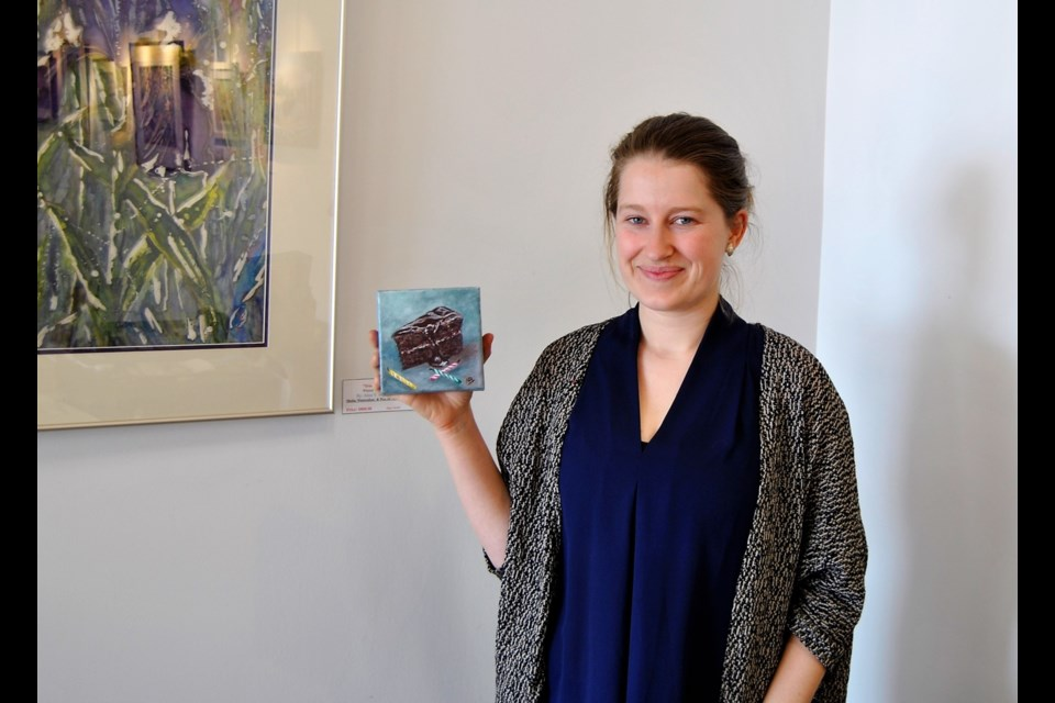 Katelyn Malo, owner of Black Spruce Gallery on Pine St. S., holds up a sample of a 5