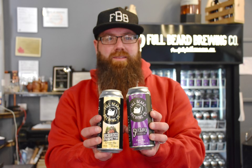 Full Beard's Jonathan St-Pierre with the two beers — Five O'Clock Shadow and The Bearded Prospector — that are being sold in eight Beer Stores in Northern Ontario. Maija Hoggett/TimminsToday