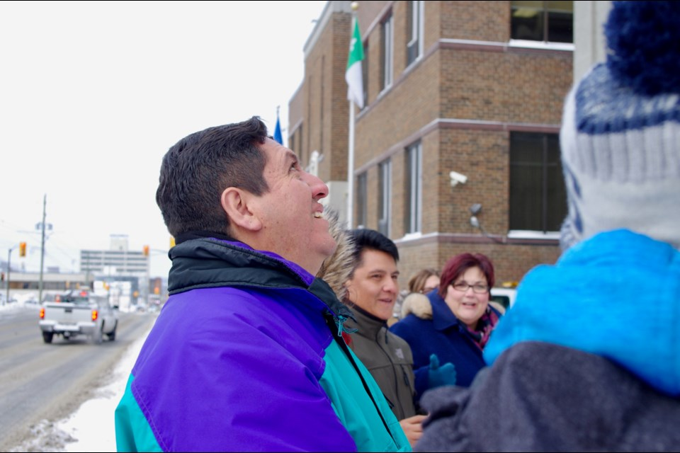 Christian Salguero, who is part of a small group from Bolivia touring Timmins this week, watches as his country's flag is raised at city hall. Maija Hoggett/TimminsToday