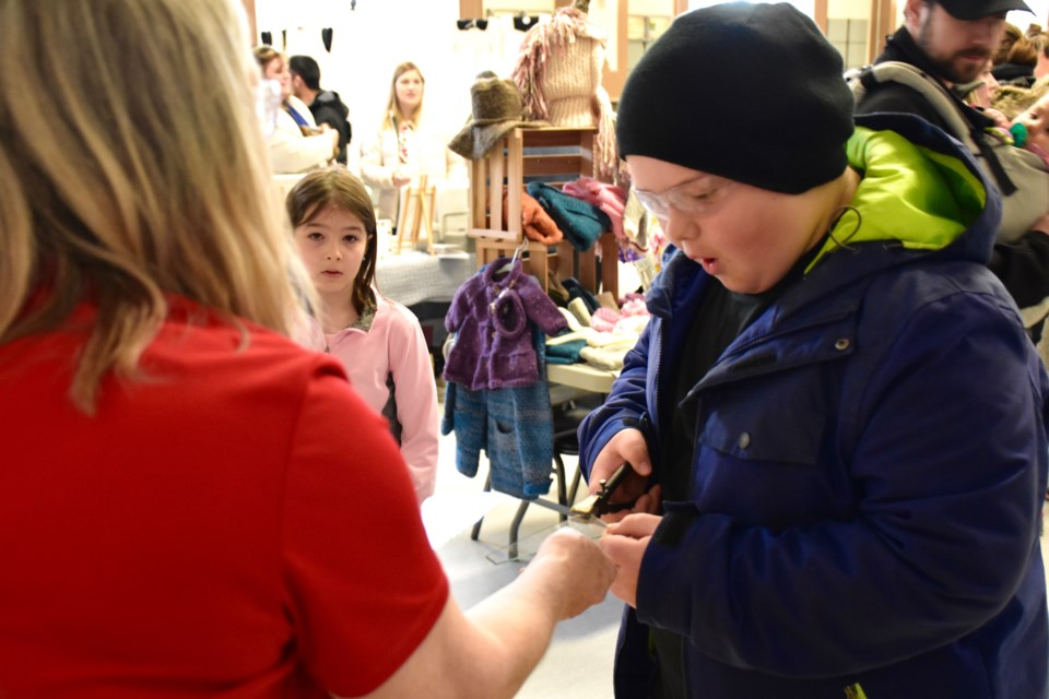 Ten-year-old Logan Wailes tries his hand at cutting glass with Thurston Stained Glass's Tanya Thurston. She is one of three vendors at the Northern Ontario Handmade market giving demonstrations. It's being held at the McIntyre Community Centre auditorium until 4 p.m. Maija Hoggett/TimminsToday