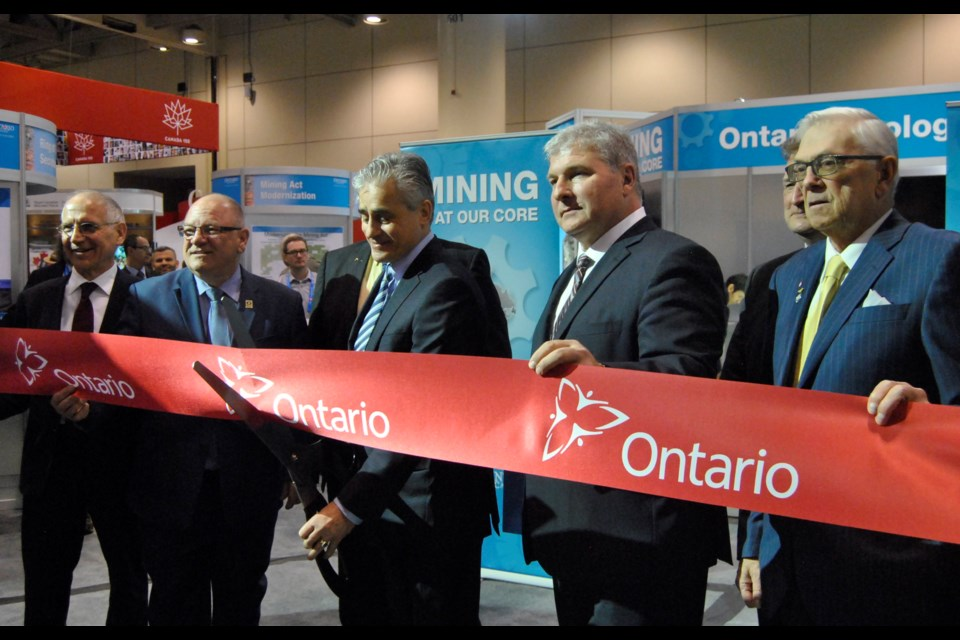 Bill Mauro, the Minister of Northern Development and Mines (third from left with the scissors) is about to cut the ribbon opening the Ontario mining pavilion at PDAC 2017. Frank Giorno for TimminsToday.