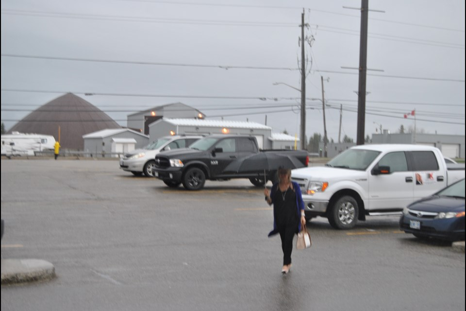It pays to carry a little insurance these days with the every changing weather that fluctuates from sunshine to rain. Insurance agent Suzanne Gallant knows -- always have an umbrella close by  -- as walks in the rain while at Timmins Square. Frank Giorno for TimminsToday.