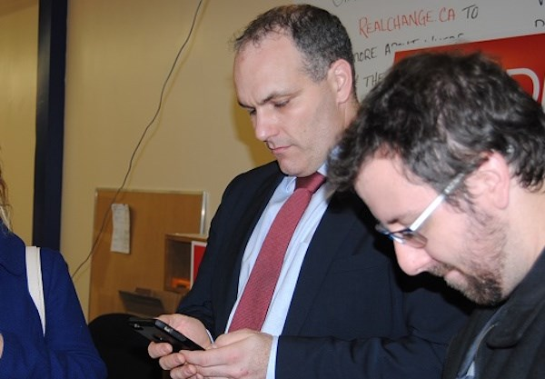 Todd Lever (left) during 2015 federal election checking results via smartphone. Frank Giorno for TimminsToday