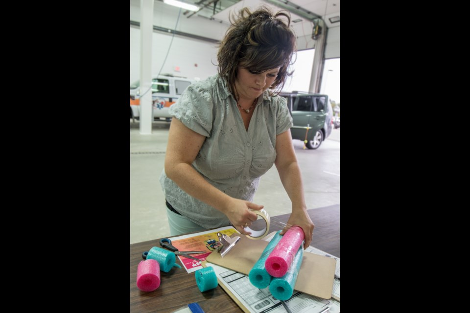 A Car Seat Technician With The Porcupine Health Unit Cuts And Binds Together Pool Noodles To