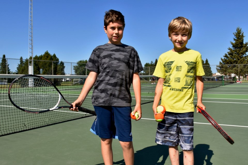 Hayden Bourgon, 12, and Ethan Harris, 10, are honing their tennis skills at the Timmins Tennis Club's free youth lessons at the Pine Street South courts. Maija Hoggett/TimminsToday